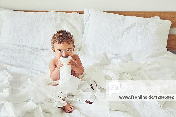 Kleinkind sitzt auf dem Bett und hält aufgetrennte Toilettenpapierrolle