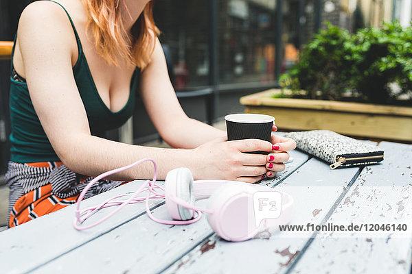 Schnappschuss einer jungen Frau  die am Tisch eines Cafés auf dem Bürgersteig sitzt
