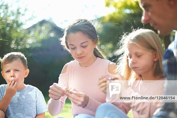 Vater und Kinder  die im Garten sitzen und Süßigkeiten essen