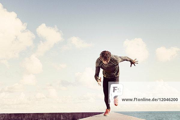 Junger Mann läuft am Deich entlang  Vorderansicht