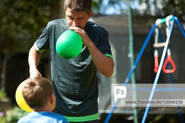 Vater und Sohn im Garten  Vater bläst Luftballons auf