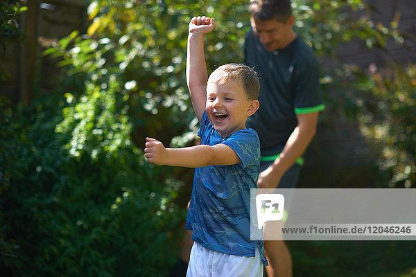 Vater und Sohn spielen im Garten