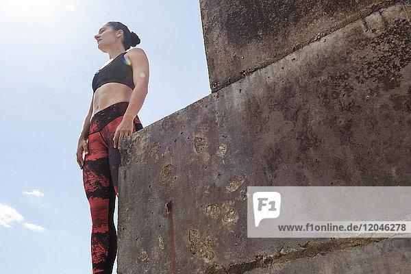 Junge weibliche Freiläuferin schaut von der Seemauer