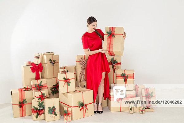 Junge Frau in rotem Kleid bei gestapelten Weihnachtsgeschenken mit Weihnachtspäckchen in der Hand