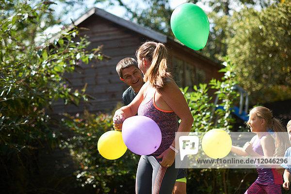 Familie spielt mit Luftballons im Garten