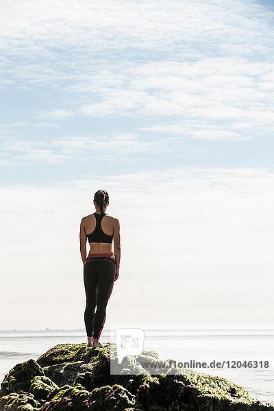 Rückansicht einer jungen Läuferin  die vom Strandfelsen auf das Meer blickt