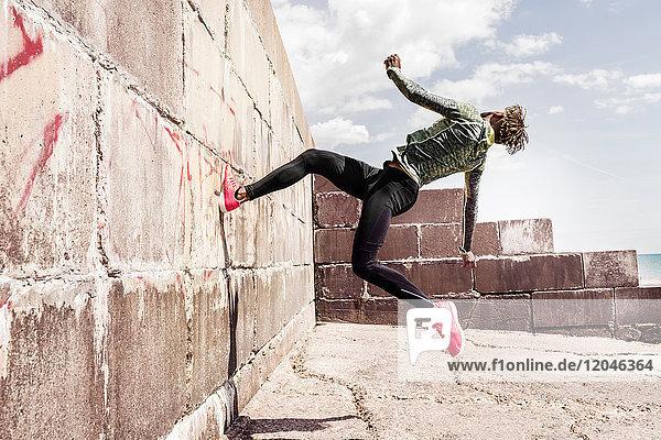Junger Mann  freilaufend  im Freien  läuft an der Wand hoch