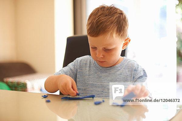 Junge Junge sitzt am Tisch und spielt mit Modelliermasse