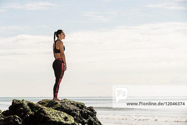 Junge Läuferin blickt vom Strandfelsen aufs Meer