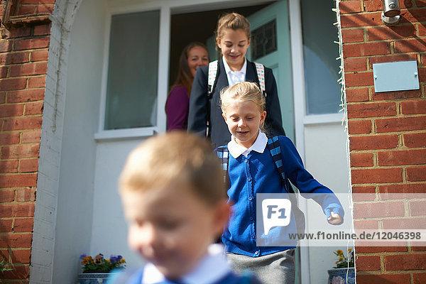 Schuljunge und Schwestern verlassen die Haustür