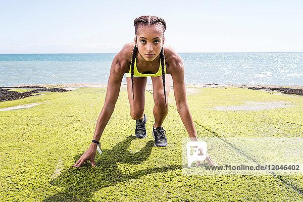Junge Frau am Meer  in Startpositionen  Vorbereitung auf den Lauf