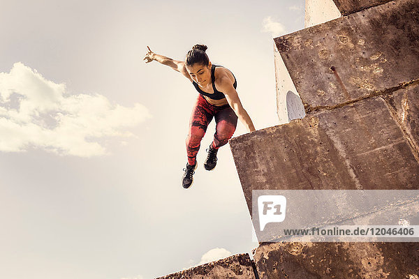 Young female free runner jumping down sea wall