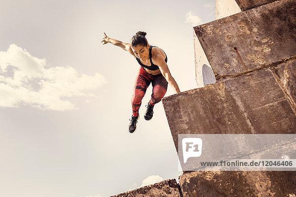 Junge weibliche Freiläuferin springt von Seedeich