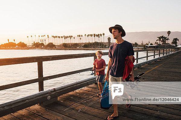 Father and son on pier with fishing rods  Goleta  California  United States  North America