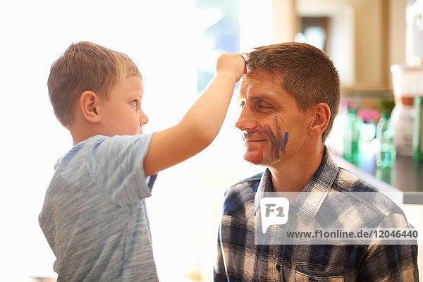 Junge malt mit Gesichtsfarbe auf das Gesicht des Vaters