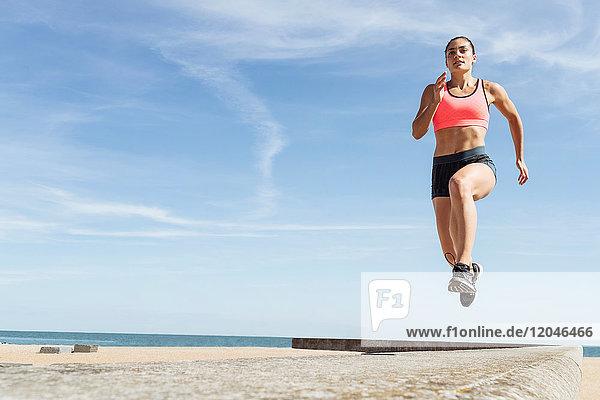 Junge Frau rennt am Deich entlang  mittlere Luft
