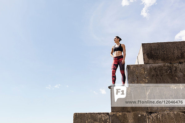 Junge weibliche Freiläuferin schaut von der Spitze des Deichs