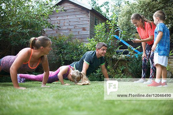 Familie übt im Garten  macht Liegestütze