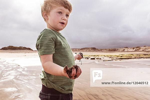 Junge am Strand mit nassem Sand in der Hand  Santa Cruz de Tenerife  Kanarische Inseln  Spanien  Europa