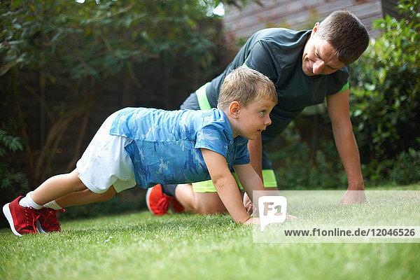 Vater und Sohn üben im Garten  machen Liegestütze