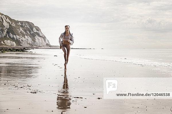 Frontansicht einer jungen Läuferin  die barfuss am Strand entlang läuft