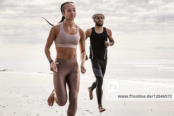 Junge männliche und weibliche Läufer laufen barfuss am Strand entlang