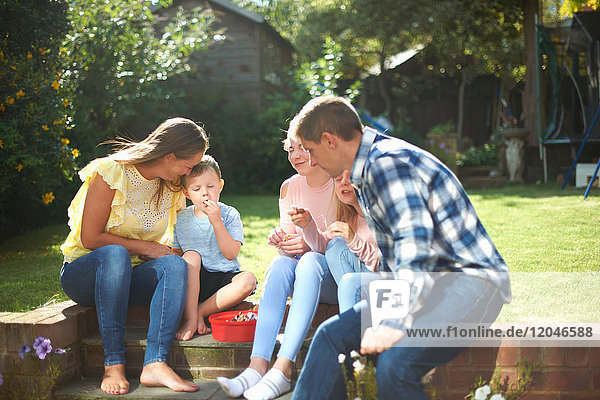 Family  sitting in garden  eating sweets