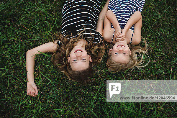 Overhead upside down portrait of girl and her sister lying on grass