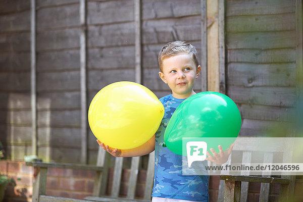 Kleiner Junge im Garten  der Luftballons hält
