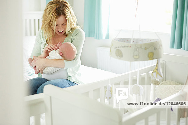 Mother sitting on bed  holding newborn baby