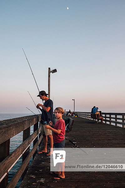 Father and son on pier fishing  Goleta  California  United States  North America