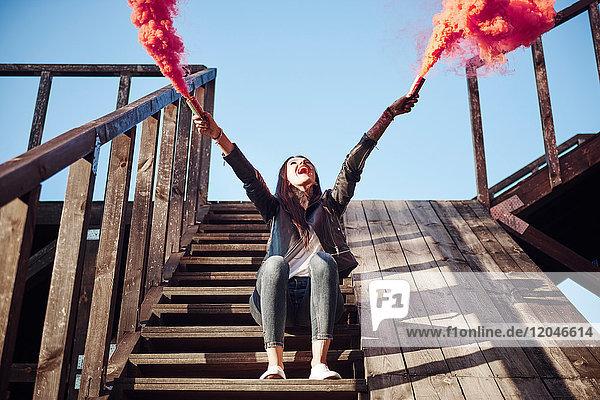 Junge Frau sitzt auf Holzstufen  hält Handfackeln in der Hand  roter Rauch strömt aus den Fackeln  niedriger Blickwinkel