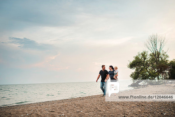 Pregnant couple strolling along beach with male toddler son  Lake Ontario  Canada