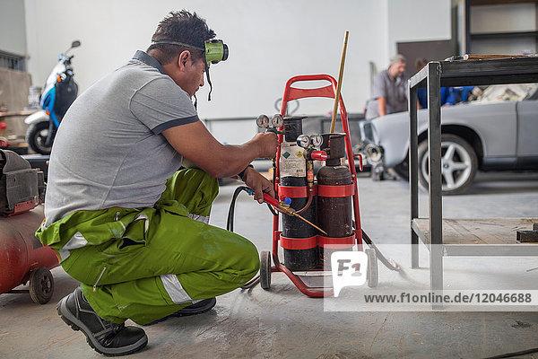 Man preparing welding jig in bodywork repair shop