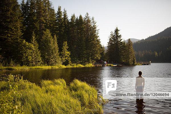 Teenager Junge im See stehend  Rückansicht