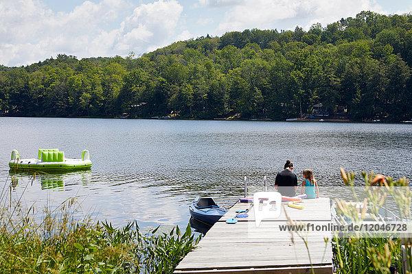 Zwei Mädchen sitzen auf einem Steg am See  Rückansicht