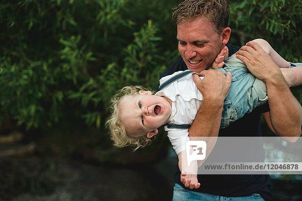Mature man holding up toddler son