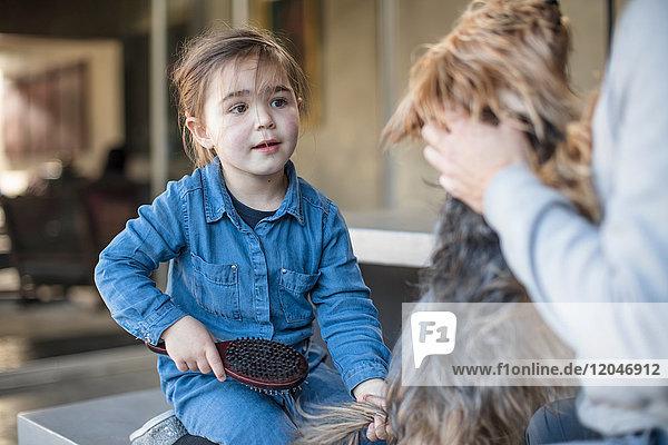 Mädchen und Vater pflegen Haushund im Wohnzimmer