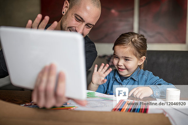 Man and daughter at table waving at digital tablet