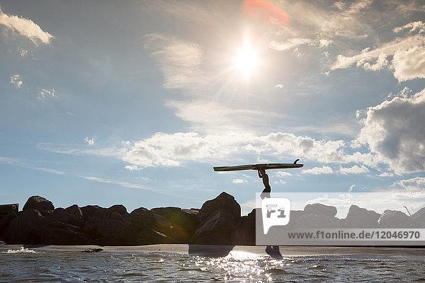 Junger Mann geht über Felsen und trägt ein Surfbrett