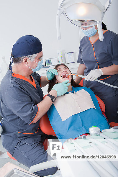 Dentist and dental nurse with patient