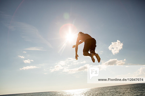 Young man jumping into water  mid air  rear view