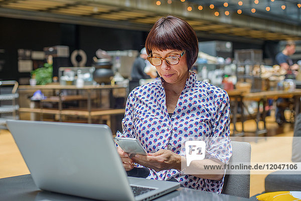 Woman in office using smartphone