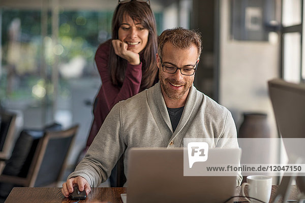 Businesswoman and man looking at laptop at home desk