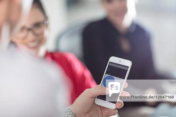 Hand eines männlichen Büroangestellten mit Smartphone