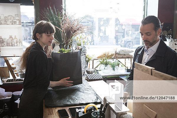 Seitenansicht der jungen Besitzerin mit Einkaufstasche  während der männliche Kunde am Ladentisch steht.