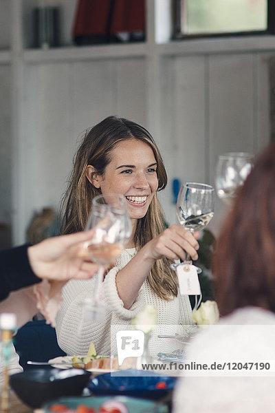 Lächelnde junge Frau  die während der Mittagsparty mit Freunden anstoßen will.