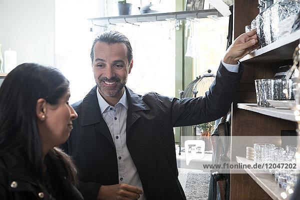 Lächelnde reife Kunden  die mit Glaswaren im Geschäft stehen und sich unterhalten