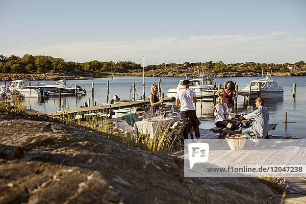 Junge multiethnische Freunde genießen den Sommer im Hafen gegen den Himmel an einem sonnigen Tag.