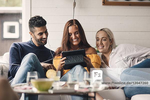 Fröhliche junge Freunde teilen sich ein digitales Tablett  während sie zu Hause auf dem Sofa sitzen.